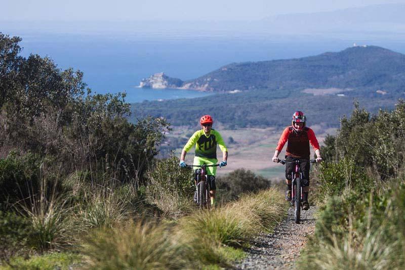 foto di sportivi su mountain bike su una collina con mare sullo sfondo