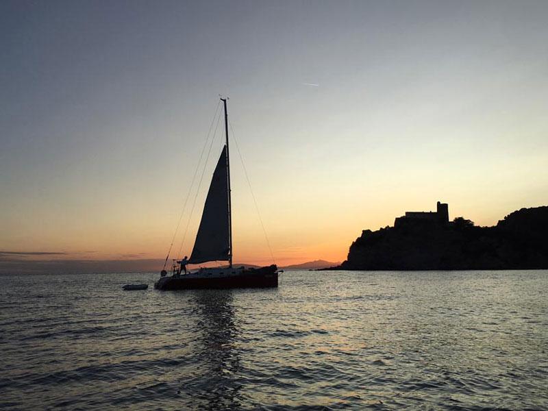 Fotografia di barca a vela al tramonto in maremma