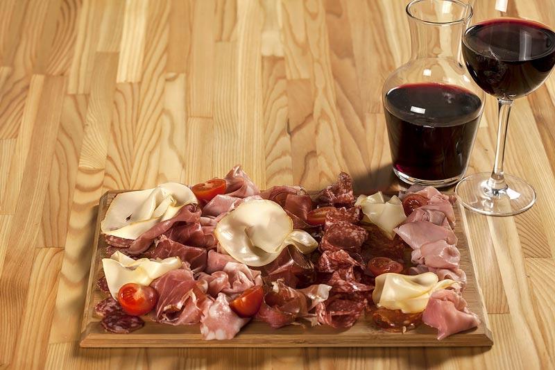 Fotografia di tagliere con affettati tipici toscani e vino