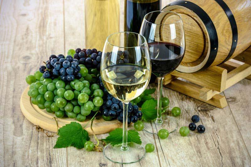 Foto professionale di vini pregiati toscani con uva e botte